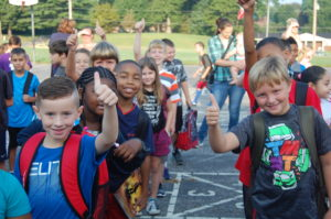 "Children wearing backpacks in a line outdoors giving ""thumbs up"""