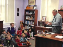 Dr. Robert Green talking to students in his office.
