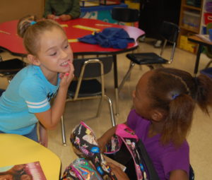 Girl pointing to her tooth to show a friend.
