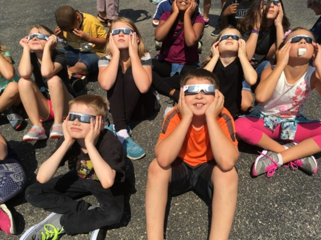 Students wearing protective glasses viewing solar eclipse