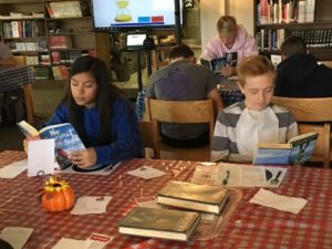 Students reading at book tasting in CHS library
