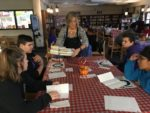 Teacher serves tray of books to students in library