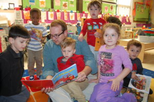 Early Childhood/Pre-K Coordinator Zach Allen reads to students