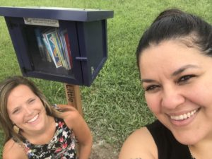 Sarah Gray and Lisa Garcia with Little Free Library box